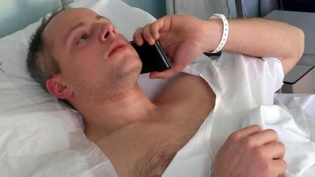 Mann liegt im Spital und telefoniert mit dem Handy.