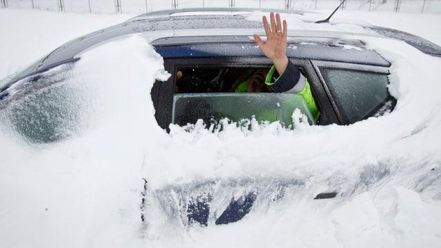 Mann in eingeschneitem Auto