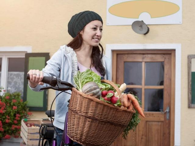 Frau kauft Gemüse mit Fahrrad