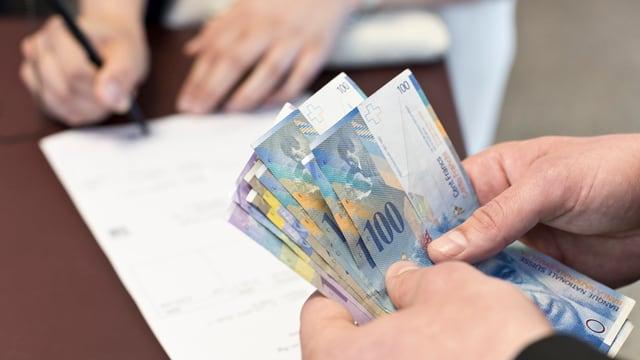 Hände, die Schweizer Banknoten auf einen Tisch legen.