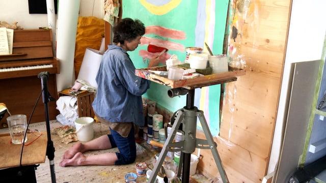Eine Frau malt kniend ein Bild.