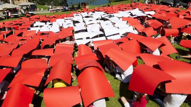 Kinder formieren sich mit farbigen Schildern zu einer grossen Schweizer Flagge.