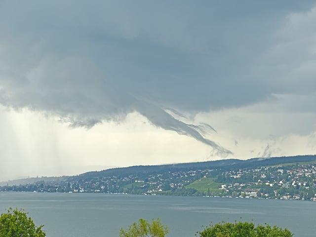 Eine, von einer Gewitterwolke ausgehende schlauchartige Wolkenfahne hängt über dem Zürichsee.