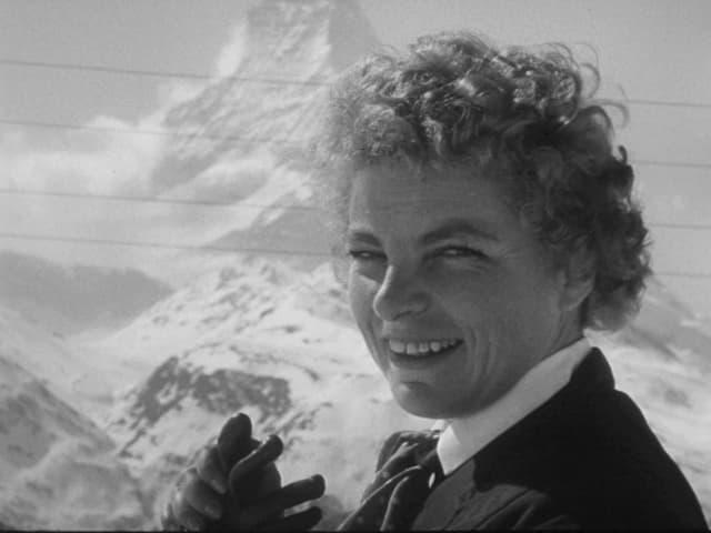 Eine Skifahrerin posiert mit ausgezogenen Handschuhen vor einem Bergmassiv.
