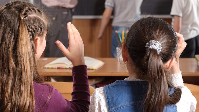 Zwei Mädchen sitzen auf der Schulbank und halten die Handhoch.