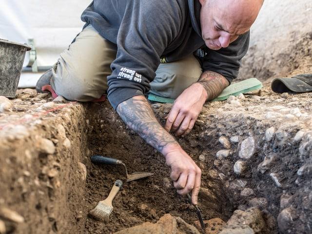Mann gräbt Grube aus