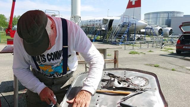Mann arbeitet im Vordergrund, im Hintergrund Flugzeug