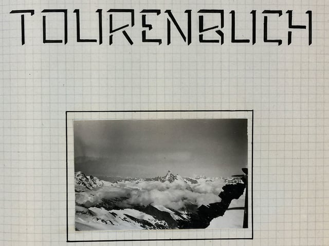 Ein altes Album zeigt ein Bild von den Bergen und trägt den Titel Tourenbuch.