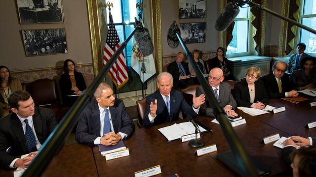 Biden und weitere politische Vertreter an einem Sitzungstisch.