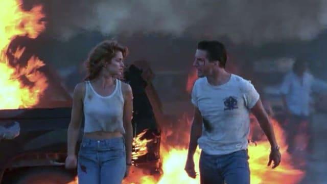 Eine Frau (links) und ein Mann (rechts) laufen in zerfetzten Kleidern von einem brennenden Auto weg.