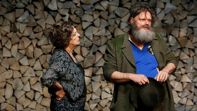 Vor einem akkurat gestapelten, riesigen Holzstapelsteht ein alterer bärtiger Mann und schaut ins Leere. Neben ihm steht eine Frau, die ihre Fäuste in die Hüfte stemmt.