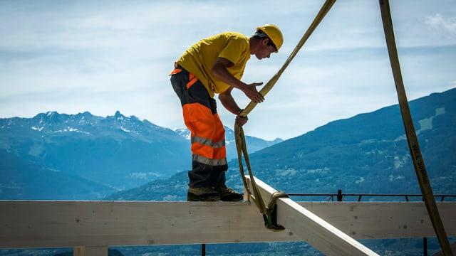Ein Bauarbeiter steht auf einem Balken auf einer Baustelle