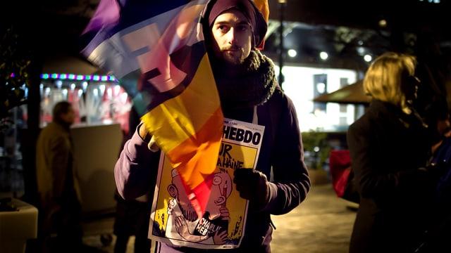 Mann mit Flagge und Satire-Magazin an Demo.