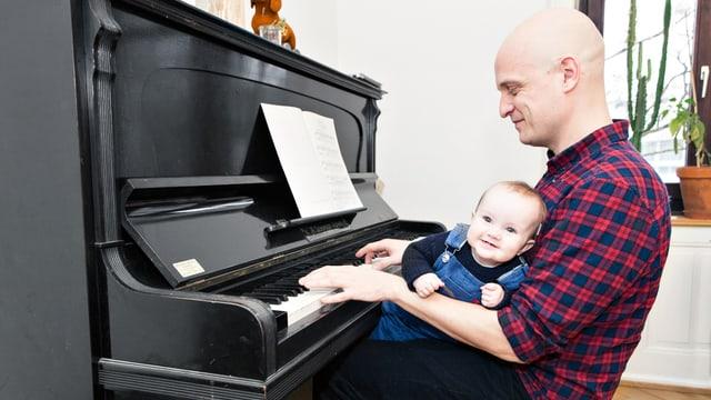 Ein Mann sitzt am Klavier mit Baby