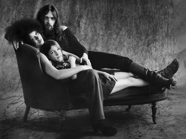 Schwarzweiss-Bild: Eine Hippie-Familie auf einem Sofa.