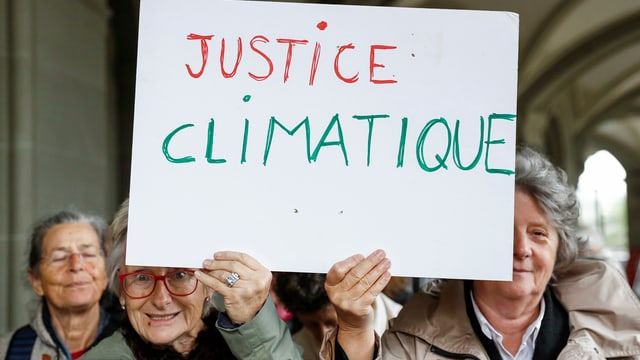 Senioras tegnan in chartun cun scret si «Justice climatique»