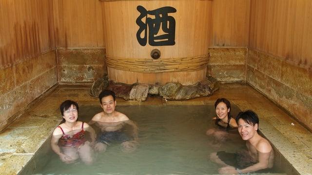 Eine Gruppe von vier jungen Japanerinnen und Japanern sitzen in einem kleinen, quadratischen Sake-Bad vor einem grossen Holzfass mit dem japanischen Reiswein.