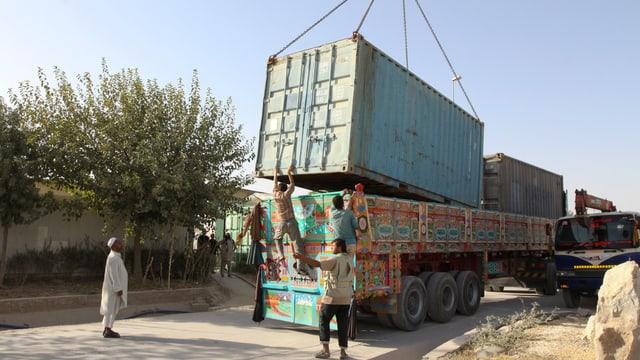 Afghanische Helfer verladen einen MIlitärcontainer der Bundeswehr auf einen Lastwagen