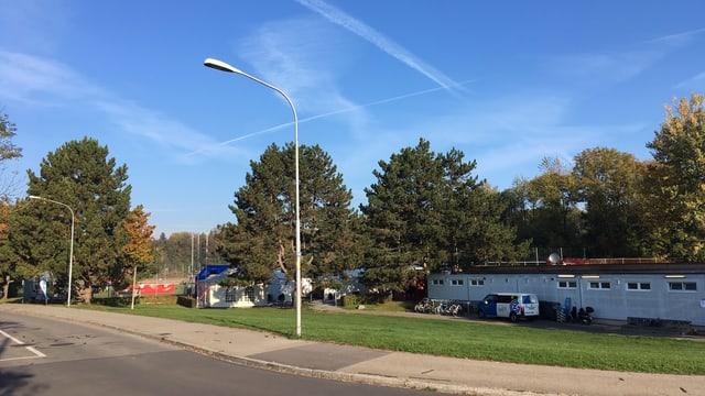 Blauer Himmel über der Sportanlage in Höngg, ein flaches Haus steht auf einer Wiese.