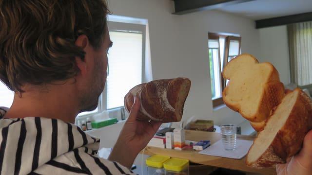 Mann hält viel Brot in den Händen