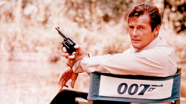 R. M. auf Stuhl sitzend mit Pistole in der Hand.