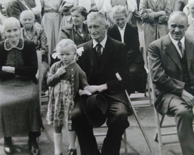 Ein kleines Mädchen steht neben ihrem Grossvater, der auf einem Stuhl sitzt.