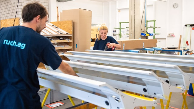 Ein Mann und eine Frau arbeiten in einer Werkhalle an speziellen Metallteilen.