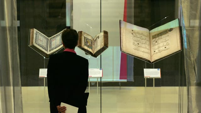 Eine Frau betrachtet eine Bibel und einen Koran.