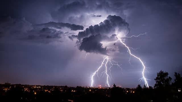 Eine Gewitterwolke und drei Blitze.