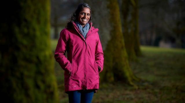 Eine Frau in pinker Regenajcke.
