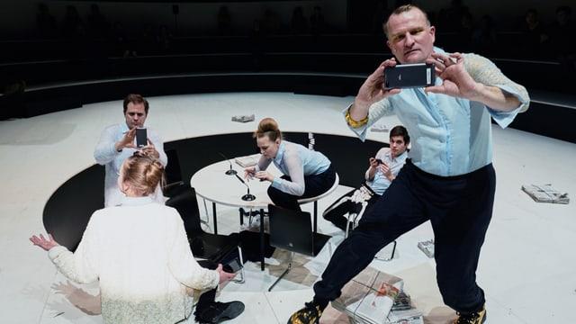 Fünf Leute auf der Bühne spielen mit ihrem Handy.