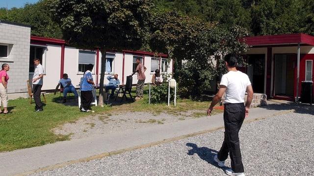Weisses Blockhaus mit Menschen im Garten