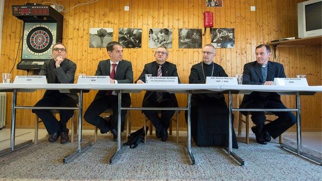 Fünf Männer sitzen an einem langen Tisch. Im Hintergrund hängen Fotos an der Wand.