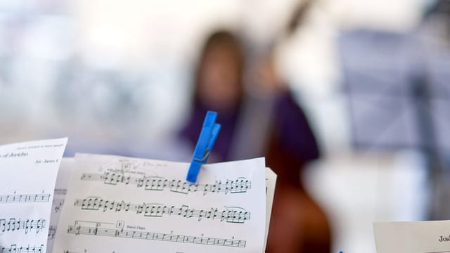 Ein Notenständer, im hintergrund verschwommen eine Cellospielerin.