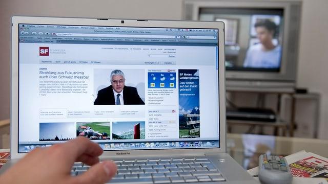 Person vor einem Laptop und TV im Hintergrund.