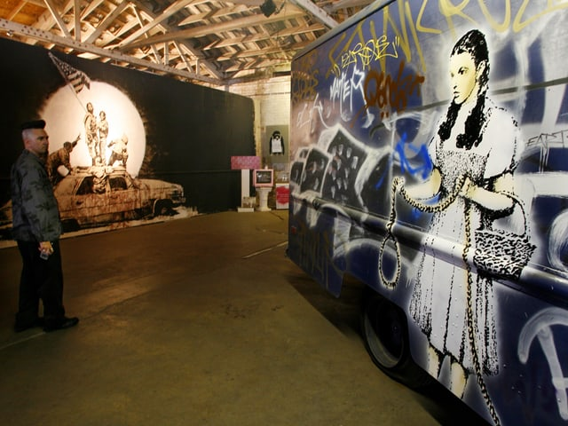Ein Truck, mit Graffitis und einem Bild der junge Schauspielerin Judy Garland bemalt, steht in einer Ausstellungshalle.