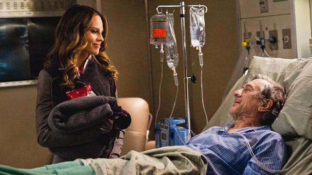 Ein alter Mann liegt in einem SPitalbett. Er hängt an infusionen. Eine junge Frau steht beim Bett.