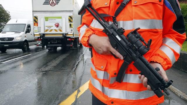 Ein Polizist steht während einer Fahndung mit seiner Waffen am Strassenrand.