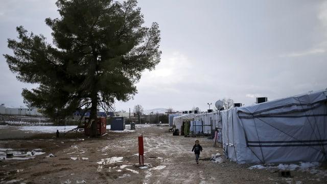 Zelte in einem morastigen Feld, teilweise liegt Schnee, ein Kind ist allein unterwegs auf einem Feldweg daneben.