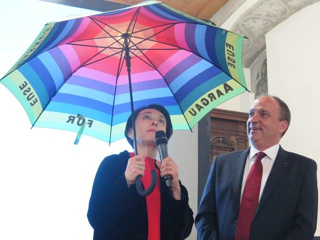 Markus Dieth wird ein Regenschirm überreicht.