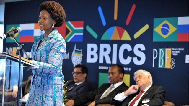 Frau an einem Rednerpult, dahinter Männer auf Stühlen und Brics-Logo.