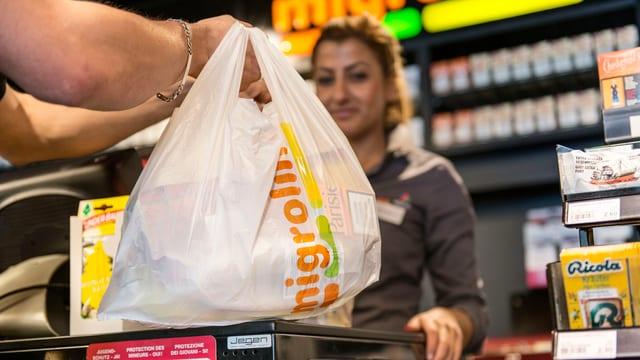 Ein Kunde an der Kasse mit einer Plastiktüte in der Hand.