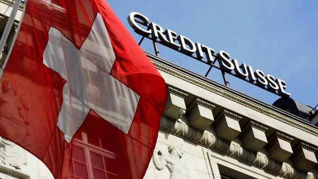 Symbolbild: Schweizer Fahne vor einem Schild der Credit Suisse.