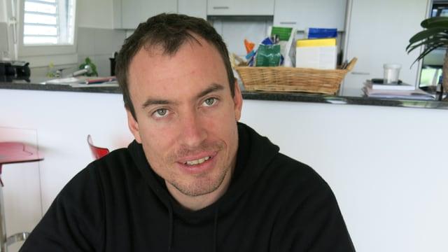 Der Eishockey-Trainer Corsin Camichel sitzt am Esstisch in seiner Wohnung.
