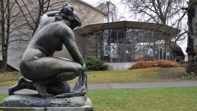 Statue auf grüner Wiese, Glasgebäude dahinter.