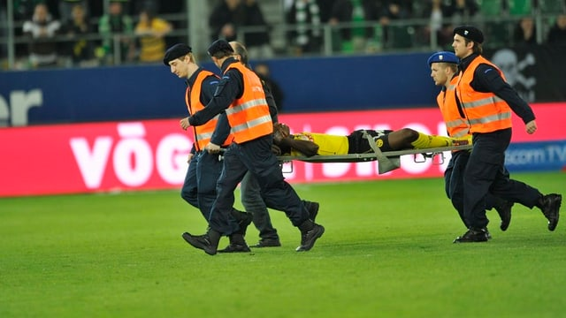 Pascal Doubai wird auf einer Trage von Helfern vom Feld gebracht.