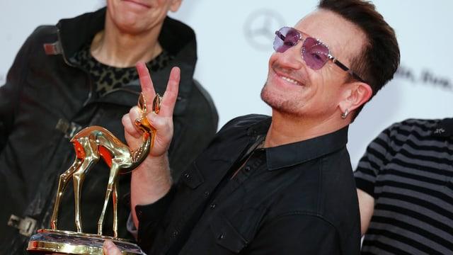 Bono strahlt und hält seinen Bambi-Preis in die Kamera.