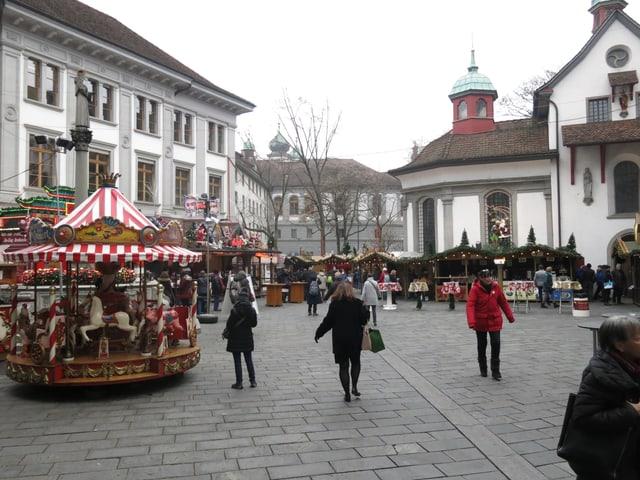 Leute laufen über einen Weihnachtsmarkt in Luzern.