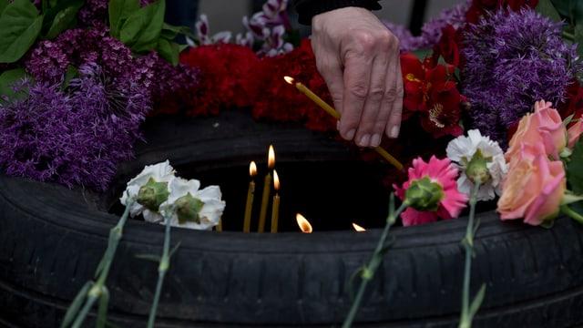 Eine Frau legt eine Kerze im Gedenken an die Opfer von Odessa nieder.