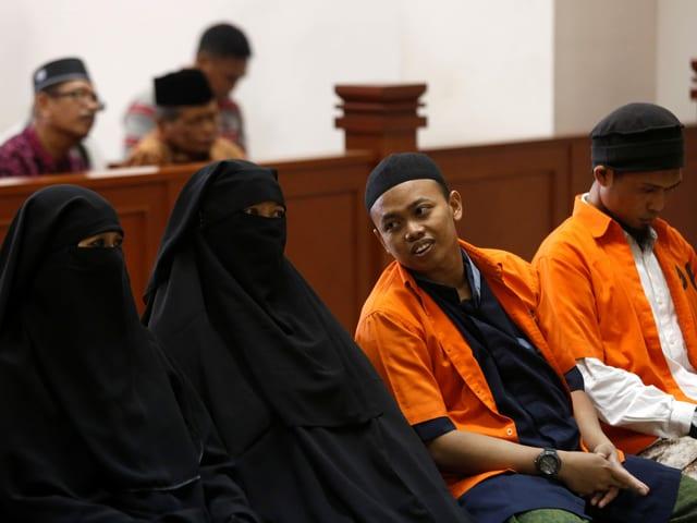 zwei Frauen in Hidschab und zwei Männer vor Gericht
